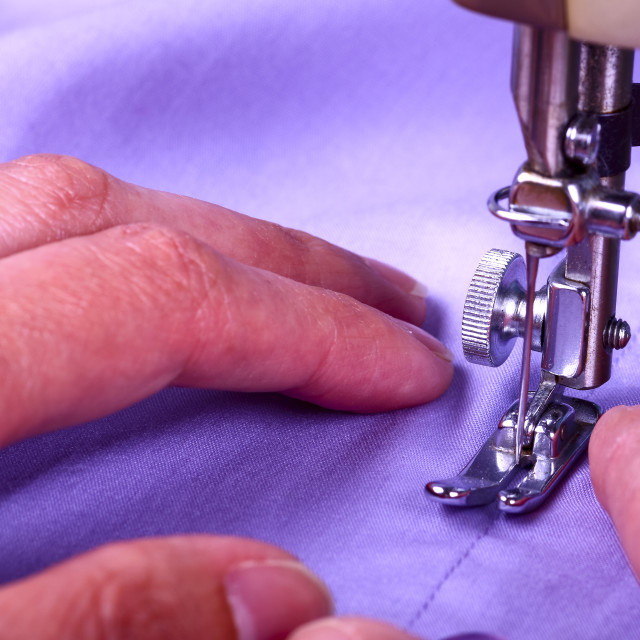 """""""Close up of a vintage sewing machine and ladies hands guiding a cotton shirt thats being stitched"""" stock image"""