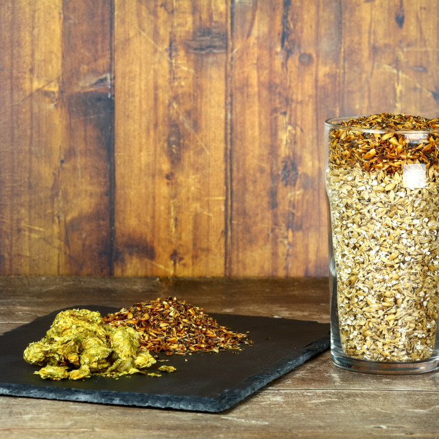 """""""Pint glass filled with barley malt the raw ingredients used to make craft ales with hops on a slate serving platter"""" stock image"""