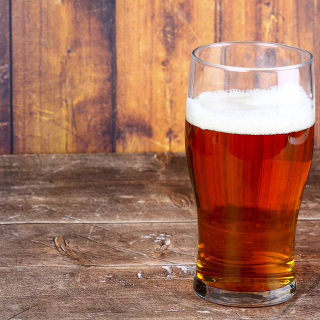 """""""Pint glass filled with craft ale on a wooden background"""" stock image"""