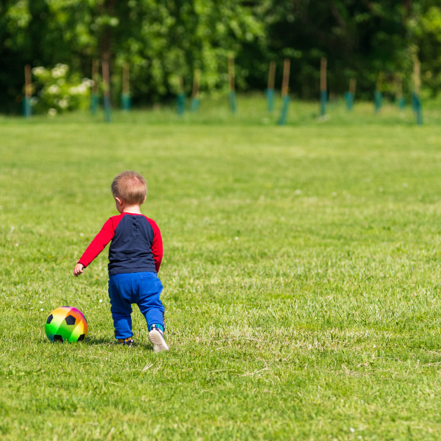 """""""A child plays with a colorful ball on a green lawn"""" stock image"""