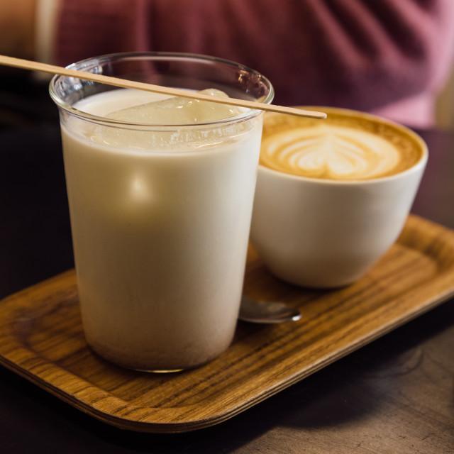 """Iced Thai tea latte in glass mug in a coffee shop."" stock image"