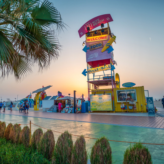 """""""aKite beach in Dubai with large running track, coffee bars and restaurants by the seaside at sunset at one of the most popular public beaches in Dubai"""" stock image"""