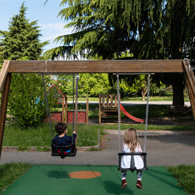 """""""Two children play on a swing in a public park"""" stock image"""