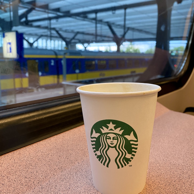 """""""Coffee to go commuting to work on train. Starbucks in carton cup. Train station through window."""" stock image"""
