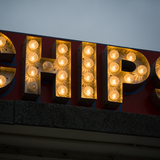 """""""Illuminated sign at seaside fish and chip shop after dark"""" stock image"""