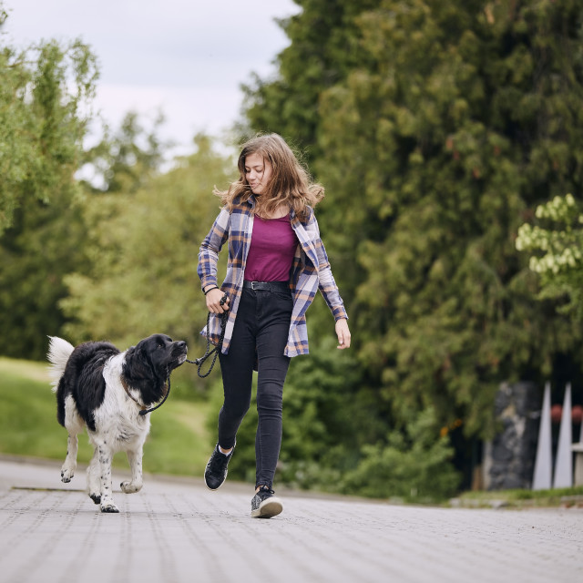 """""""Happy girl running with her dog down street"""" stock image"""