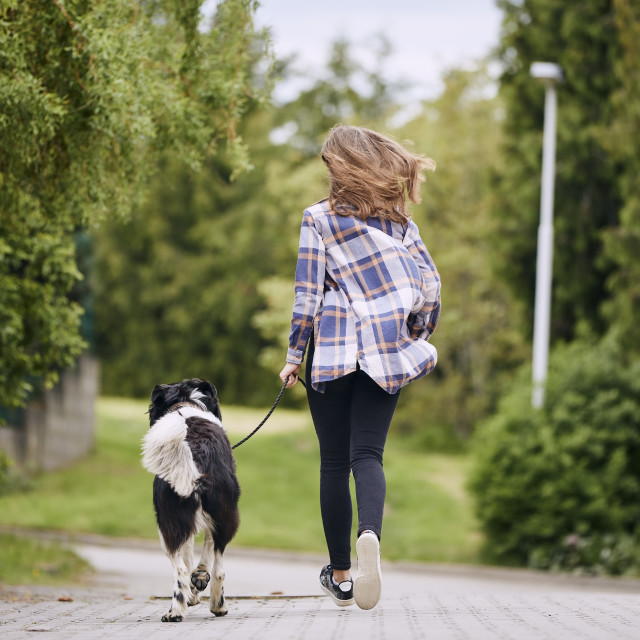"""""""Rear view of teenage girl running with her dog down street"""" stock image"""