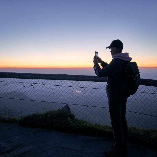 """""""Traveler photographing beautiful landscape by phone"""" stock image"""