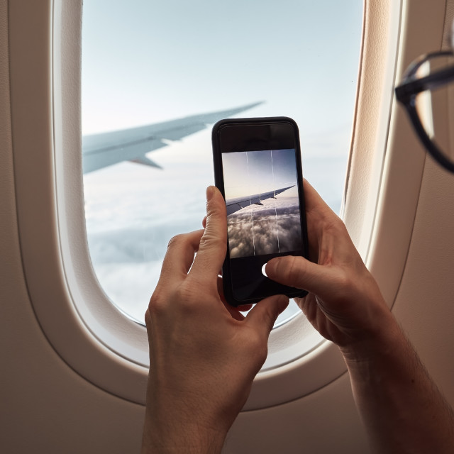 """Passenger photographing through airplane window"" stock image"