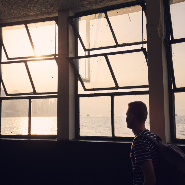 """""""Pensive man looking through window from ferry terminal"""" stock image"""