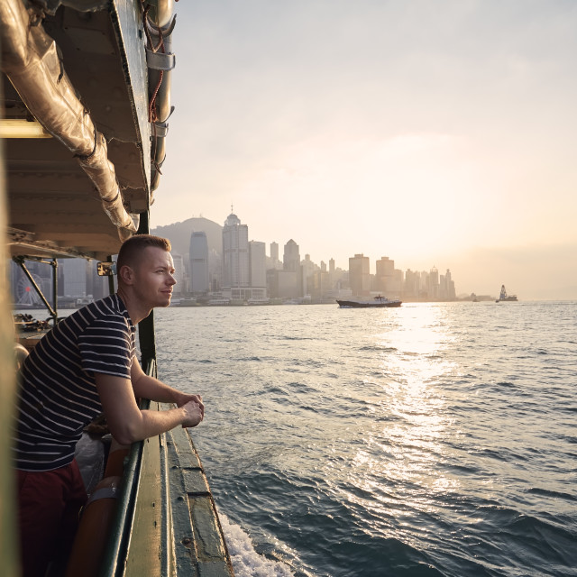 """""""Pensive man looking from ferry boat against urban skyline"""" stock image"""
