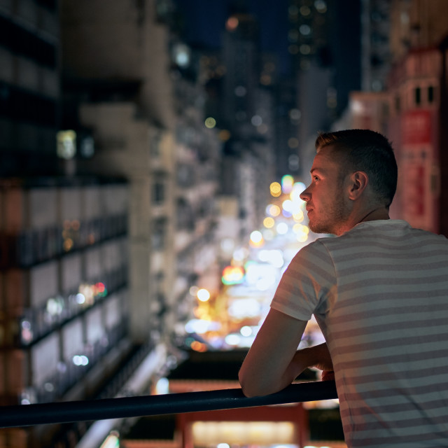 """Man enjoying night city view from balcony"" stock image"