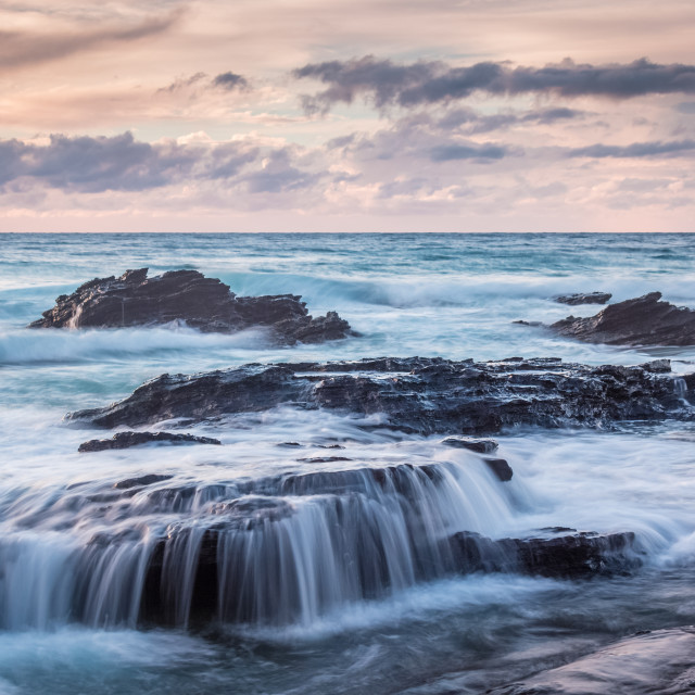 """""""Waves across the rocks in the sunrise"""" stock image"""