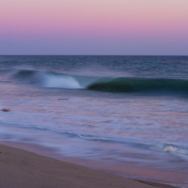 """Pink sunset over a crashing wave in Malibu"" stock image"