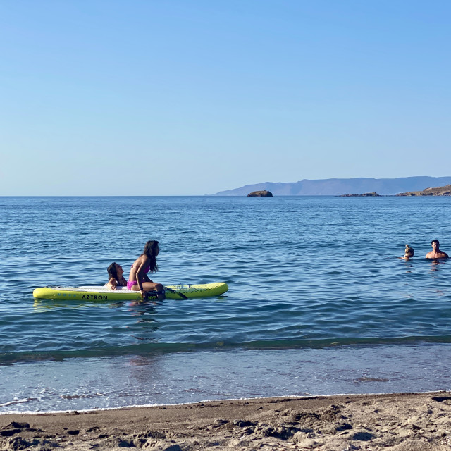 """""""Young woman wearing a pink bikini sitting relaxing with friend sup board at sea."""" stock image"""
