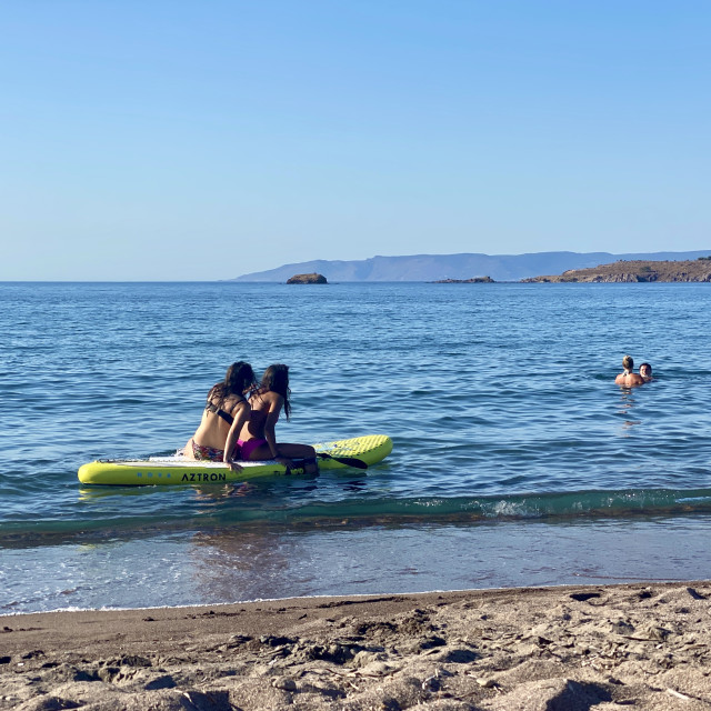 """""""Two young women friends at sea wearing bikini sitting and relaxing on a sup board by the beach."""" stock image"""