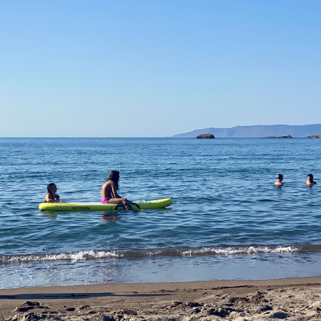 """Young woman wearing a pink bikini sitting on a yellow sup board at sea."" stock image"