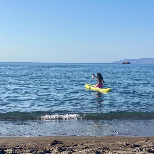 """Young woman wearing a pink bikini kneeling on a yellow sup board at sea."" stock image"