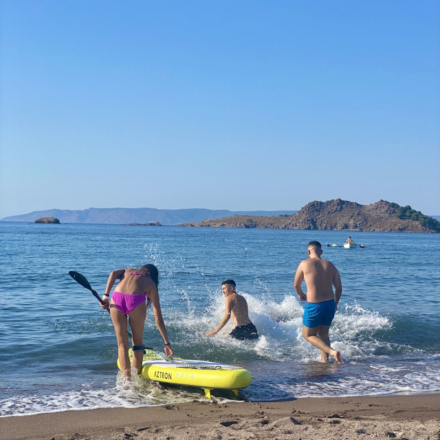 """""""Young woman wearing a pink bikini on the beach with a sup board, youths jump in the sea."""" stock image"""
