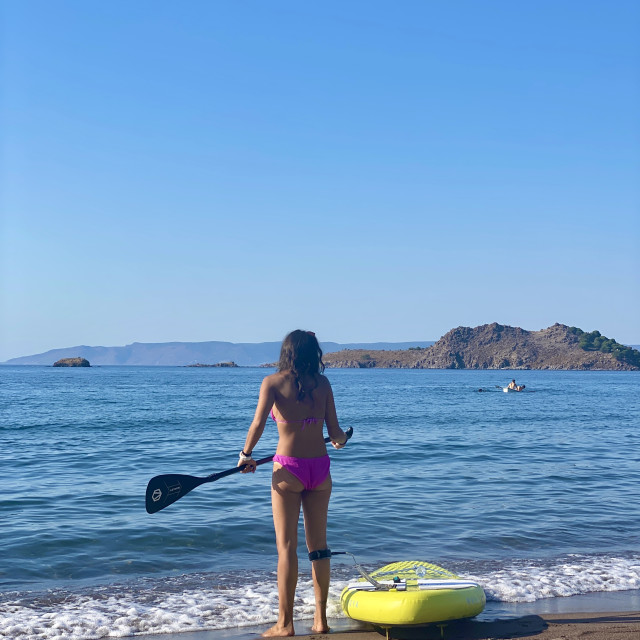 """""""Young woman wearing a pink bikini standing on the beach with a yellow sup board attached."""" stock image"""