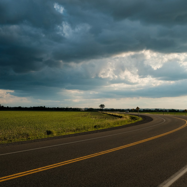 """""""Curved road with dramatic summer storm clouds"""" stock image"""