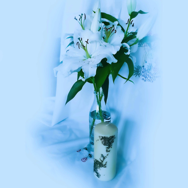 """""""White Lily flowers in. a glass bottle and a white candel"""" stock image"""
