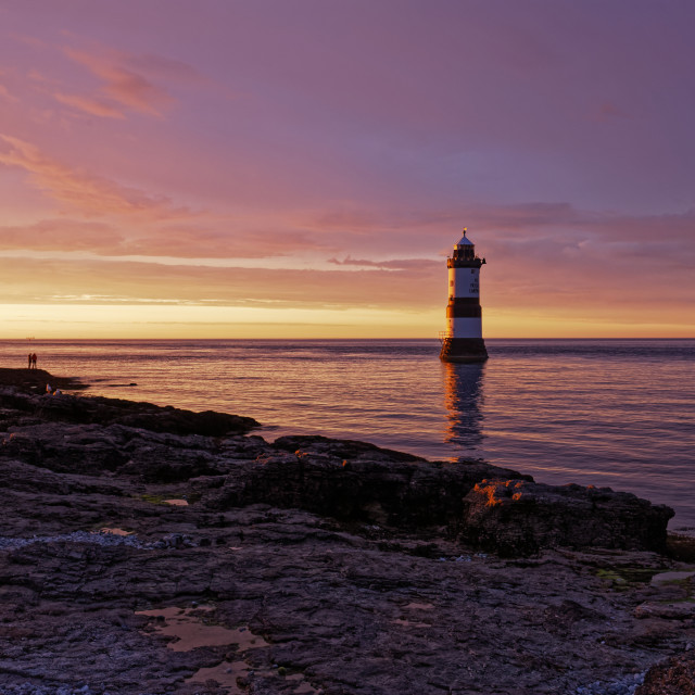 """""""People at Penmon Lighthouse during sunset"""" stock image"""