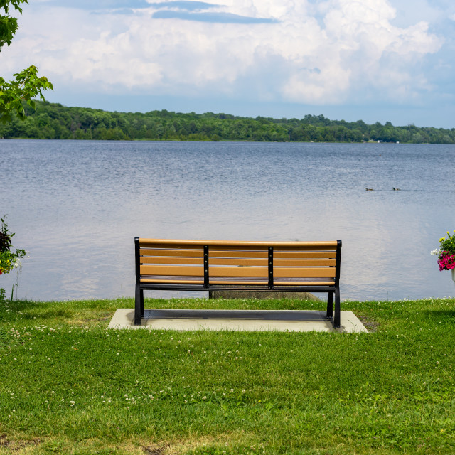 """""""Empty park bench facing river"""" stock image"""