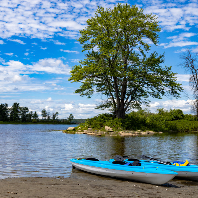 """""""Two blue kayaks resting on the beach by an island"""" stock image"""