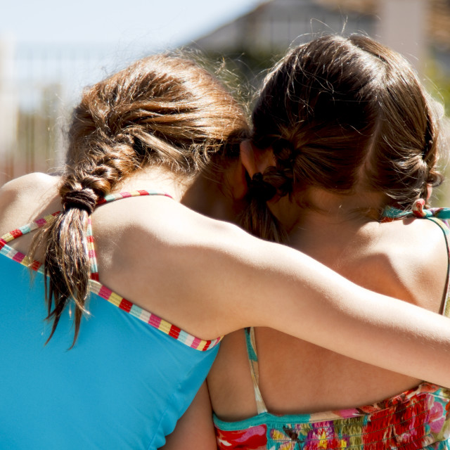 """""""Two sisters ebracing by the pool"""" stock image"""