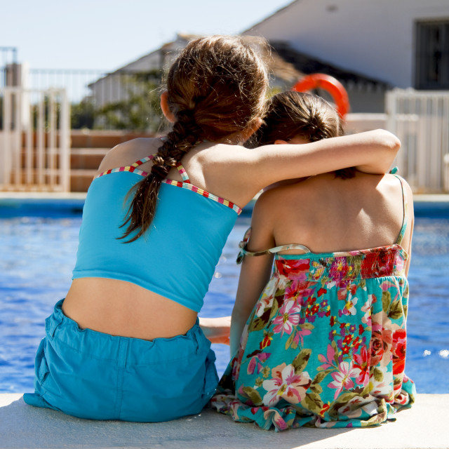 """""""Two girls ebracing by the pool"""" stock image"""