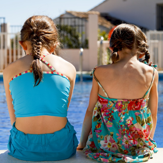 """""""Two sisters stitting by the pool"""" stock image"""