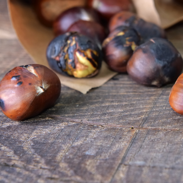 """""""roasted chestnuts spilled on wooden table"""" stock image"""