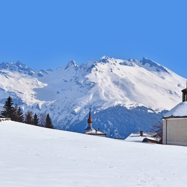 """""""chapel in a rural village between field and mountain covered with snow in winte"""" stock image"""