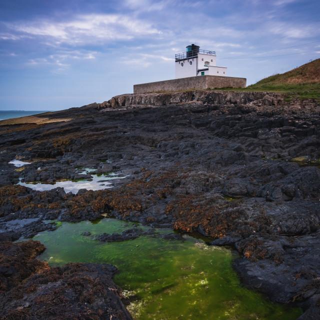 """Illuminated in green at Bamburgh Lighthouse, Northumberland"" stock image"