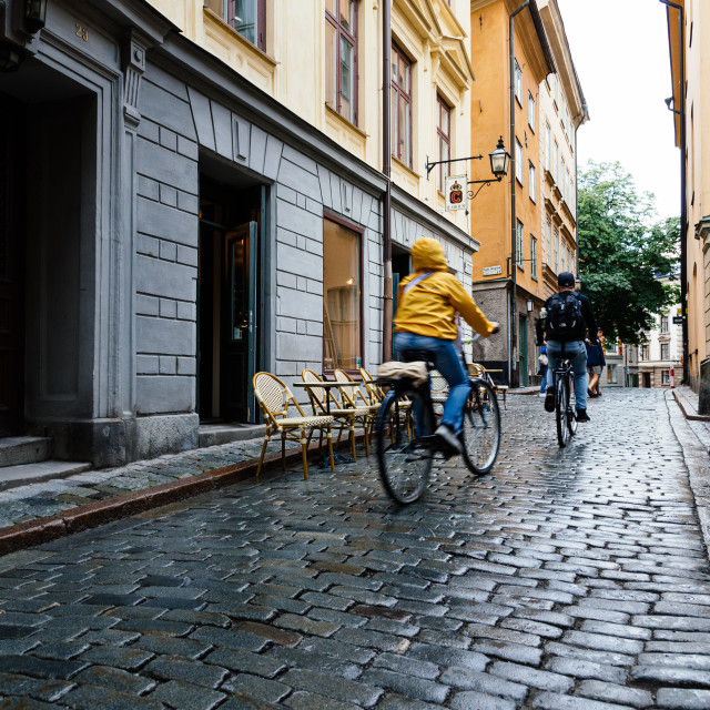 """""""People riding bicycles in cobblestoned street in Gamla Stan in Stockholm"""" stock image"""