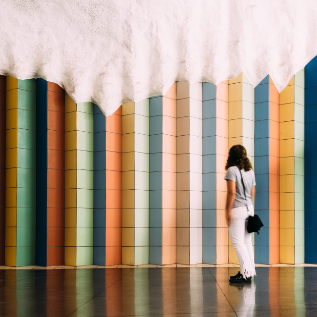 """""""Woman looking at tile colorful pattern in T-Centralen Stockholm underground"""" stock image"""
