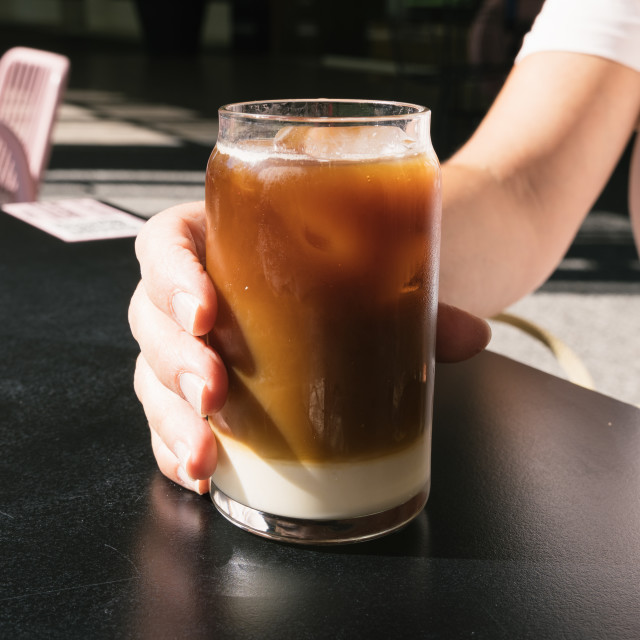 """""""Woman hand holding tasty glass of cold brew coffee with milk"""" stock image"""