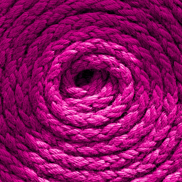 """""""Heavy-duty magenta pink coiled ships rope looking from above. Round shapes for concept & copy space."""" stock image"""