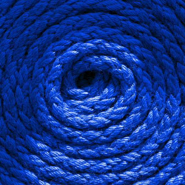 """""""Heavy-duty bright blue coiled ships rope looking from above. Round shapes for concept & copy space."""" stock image"""