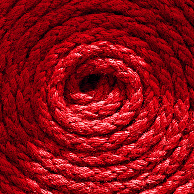 """""""Heavy-duty bright red coiled ships rope looking from above. Round shapes for concept & copy space."""" stock image"""