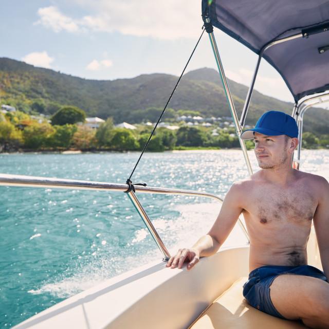 """""""Man enjoying travel on bow of motorboat"""" stock image"""