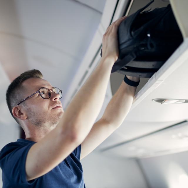 """""""Man putting hand baggage in lockers above seats of plane"""" stock image"""