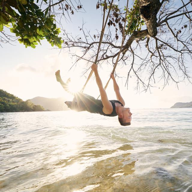 """Man on swing enjoying sunny day on beach"" stock image"