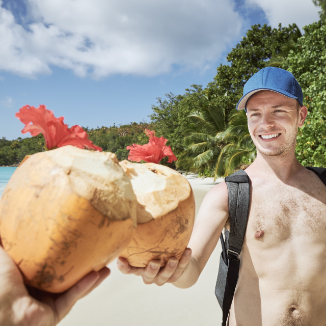 """""""Friends drinking coconut drink together on beach"""" stock image"""