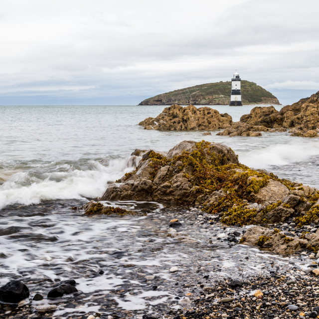 """""""Rocks lead up to Penmon Lighthouse"""" stock image"""