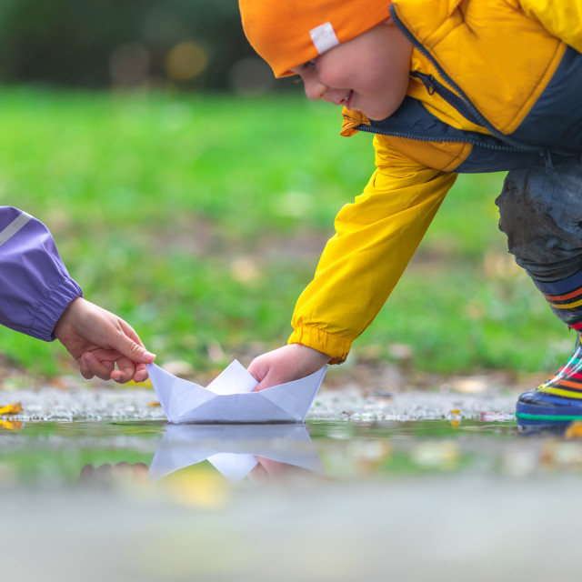 """""""Happy kids girl and boy and colorful rubber boots playing with p"""" stock image"""