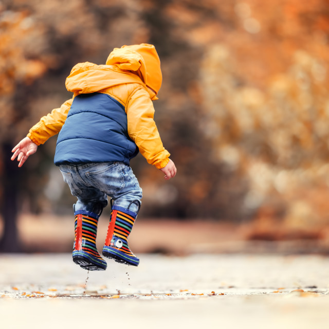 """""""Happy little kid boy jumping on rainy puddle in autumn park"""" stock image"""