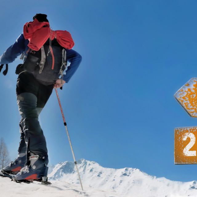 """""""2022 written on a postsign with a man in touring ski climbing snowy and sunny mountain"""" stock image"""