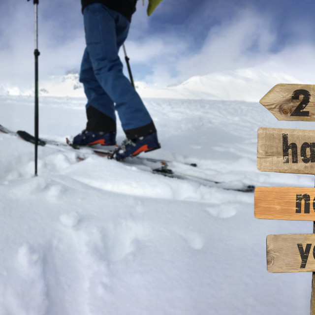 """""""2022 happy new year written on a postsign with a man in touring ski background climbing snowy mountain"""" stock image"""
